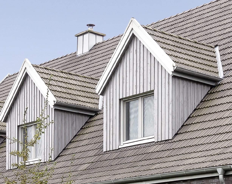 Detailansich eines Satteldaches mit Braunen Ziegeln.